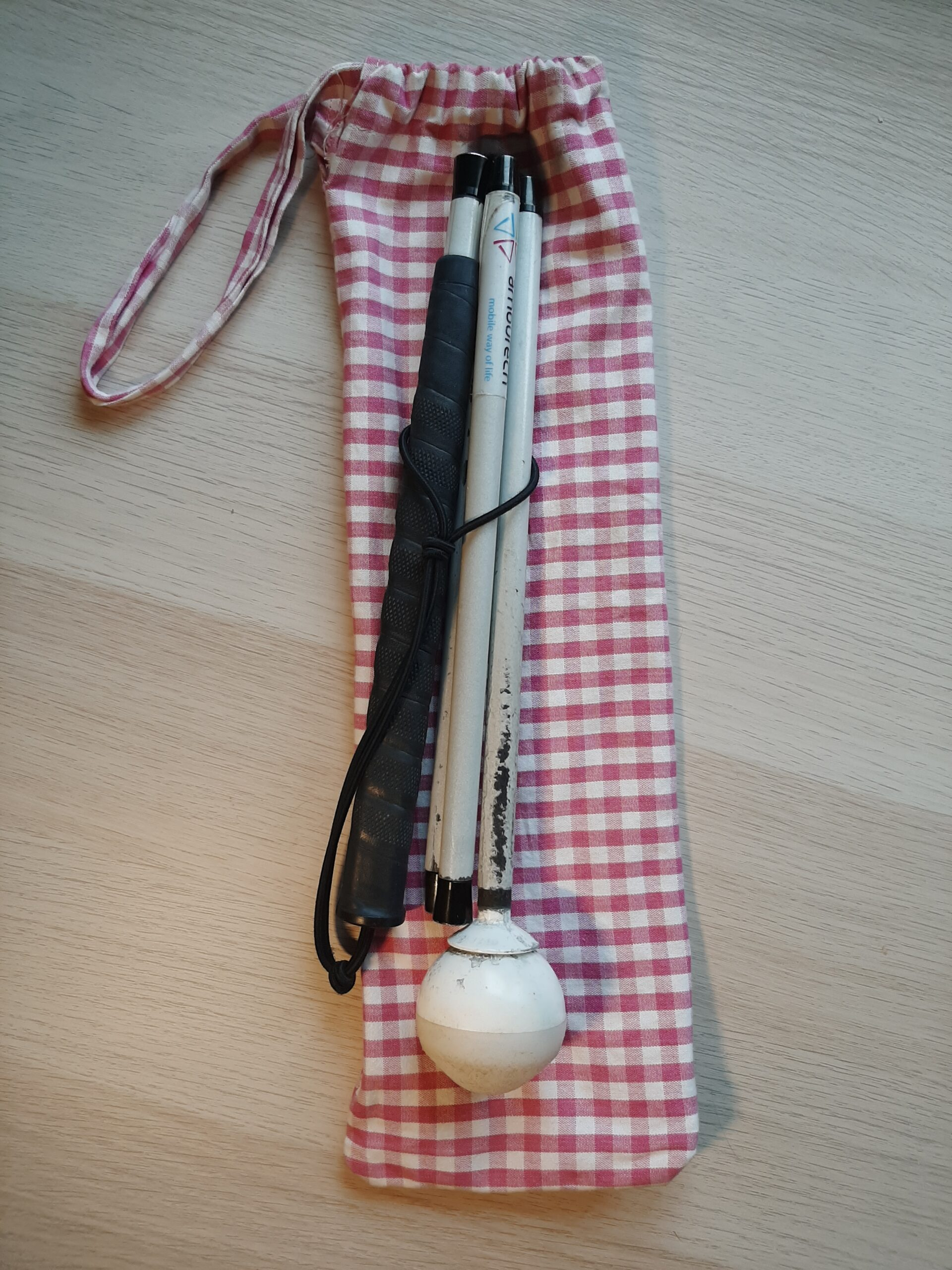 long mobility cane with pouch made from red gingham fabric