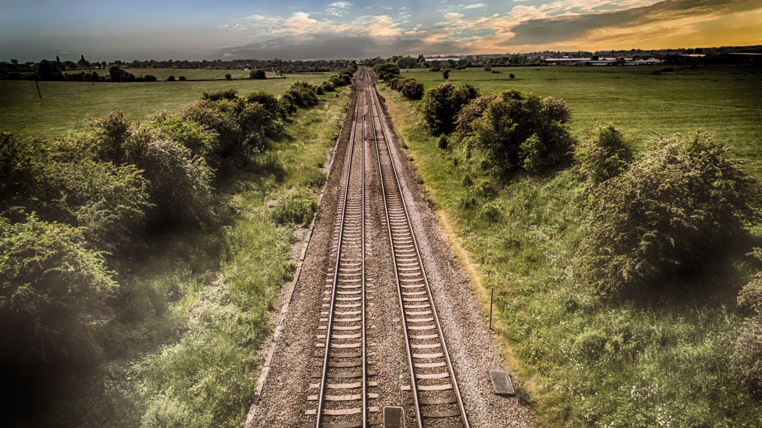 train tracks thinning to vanishing point through landscape with
